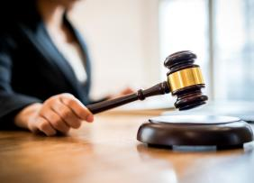 Close-Up Of Woman Holding Gavel On Table