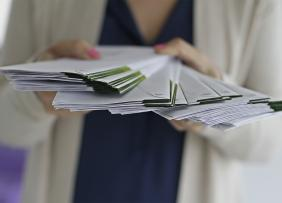 A woman holding a stack of envelopes