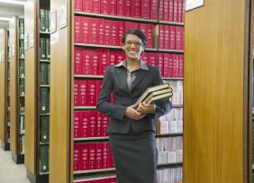 Woman in a suit holding books in a law library