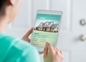Woman looking at a home listing on a tablet