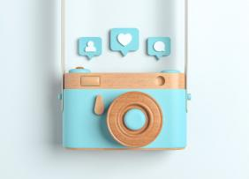 Wooden camera with Instagram icons above it