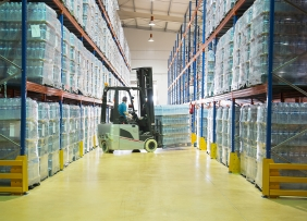A worker moving pallets with a forklift in a warehouse