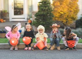 Young trick or treaters sitting on a curb