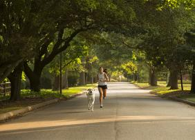 Young woman and dog jogging in a residential neighborhood