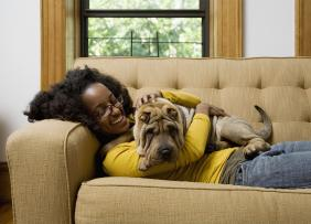 Young woman relaxing on couch with dog