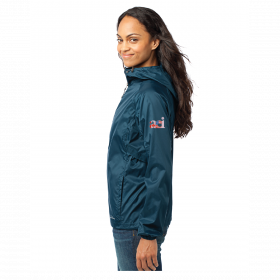 Woman standing wearing the green 2020 AEI Windbreaker jacket from a side view