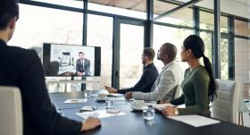 Professional businesspeople sitting in an office watching a video conference