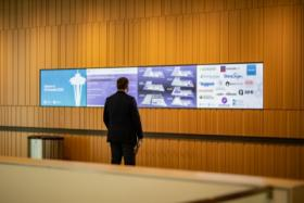 Business man standing in front of 4 screens w/sponsor logos iOi Summit 2020