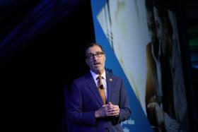 Vince Malta on stage in front of a screen, delivering the keynote at Leadership Summit 2019