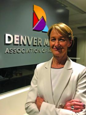 Image of Ann Turner in a white blazer in front of the Denver Metro Association of REALTORS® sign