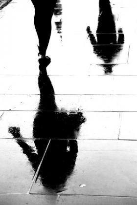 Persons Shadow Reflecting on Wet Pavement