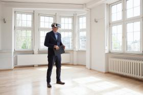 Business man in an empty room with virtual reality mask on