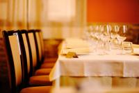 Image of a table, chairs and wine glasses at a fancy dinner setting.